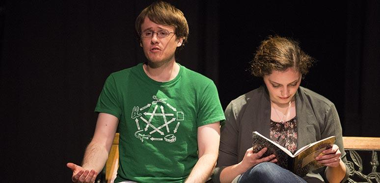 A female and male student sit on a bench as she reads to him in a theatrical performance