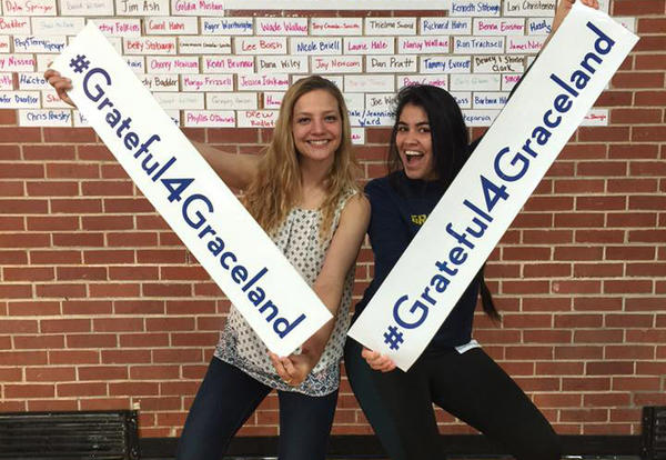 Two female students show off the #Grateful4Graceland signs