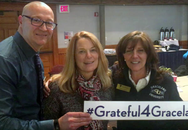 Joe Booz '86, Michele Black '81 and Holly Caskey '81share the #Grateful4Graceland sign