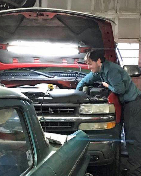 A Hunterdon Prep student working as an intern in an auto service center.