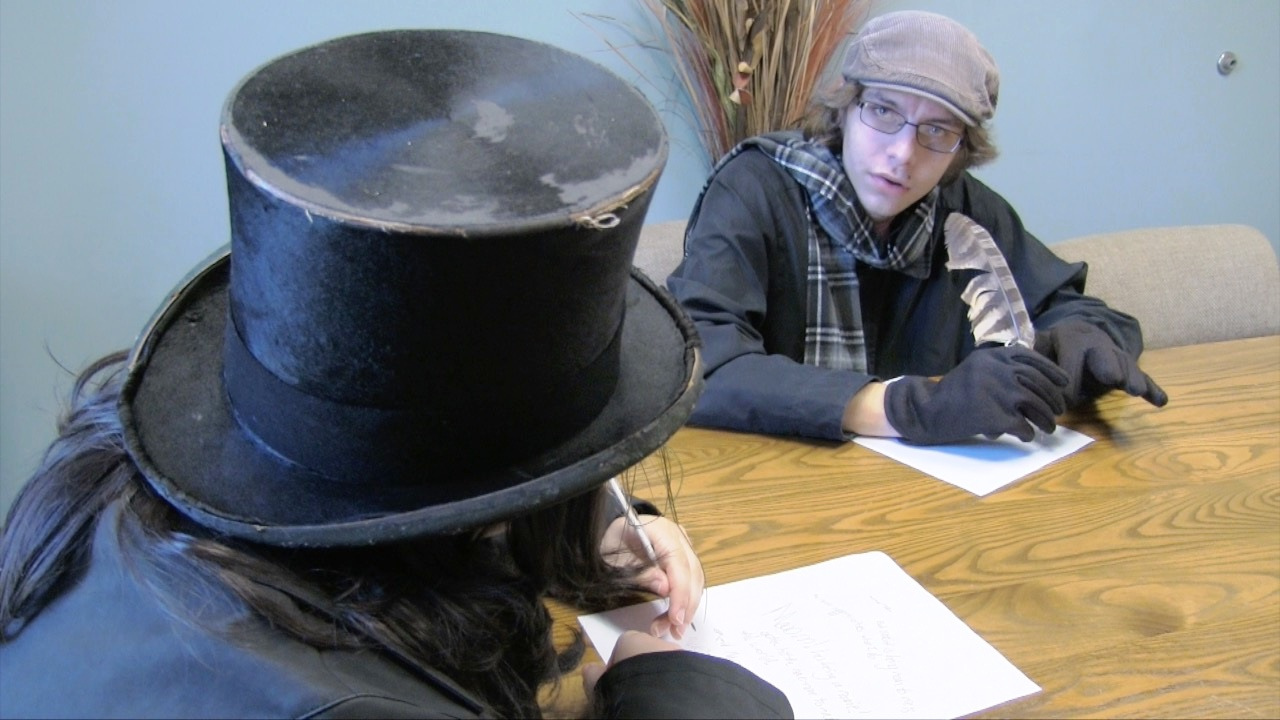 Two students dressed in Dickens costumes working on a theater performance