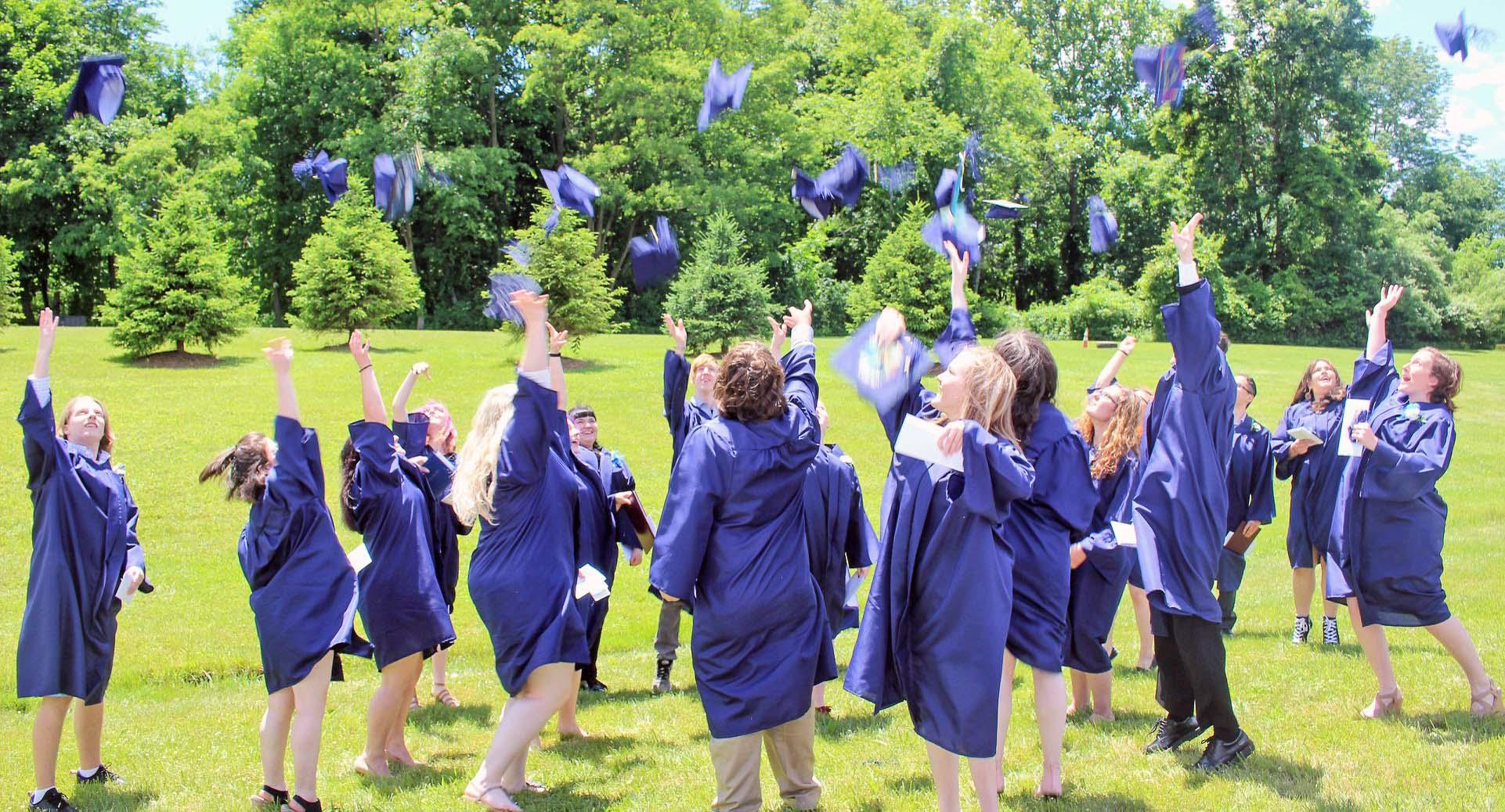 A large group of Hunterdon Prep students in their graduation gowns throwing their caps into the air after the graduation ceremony.