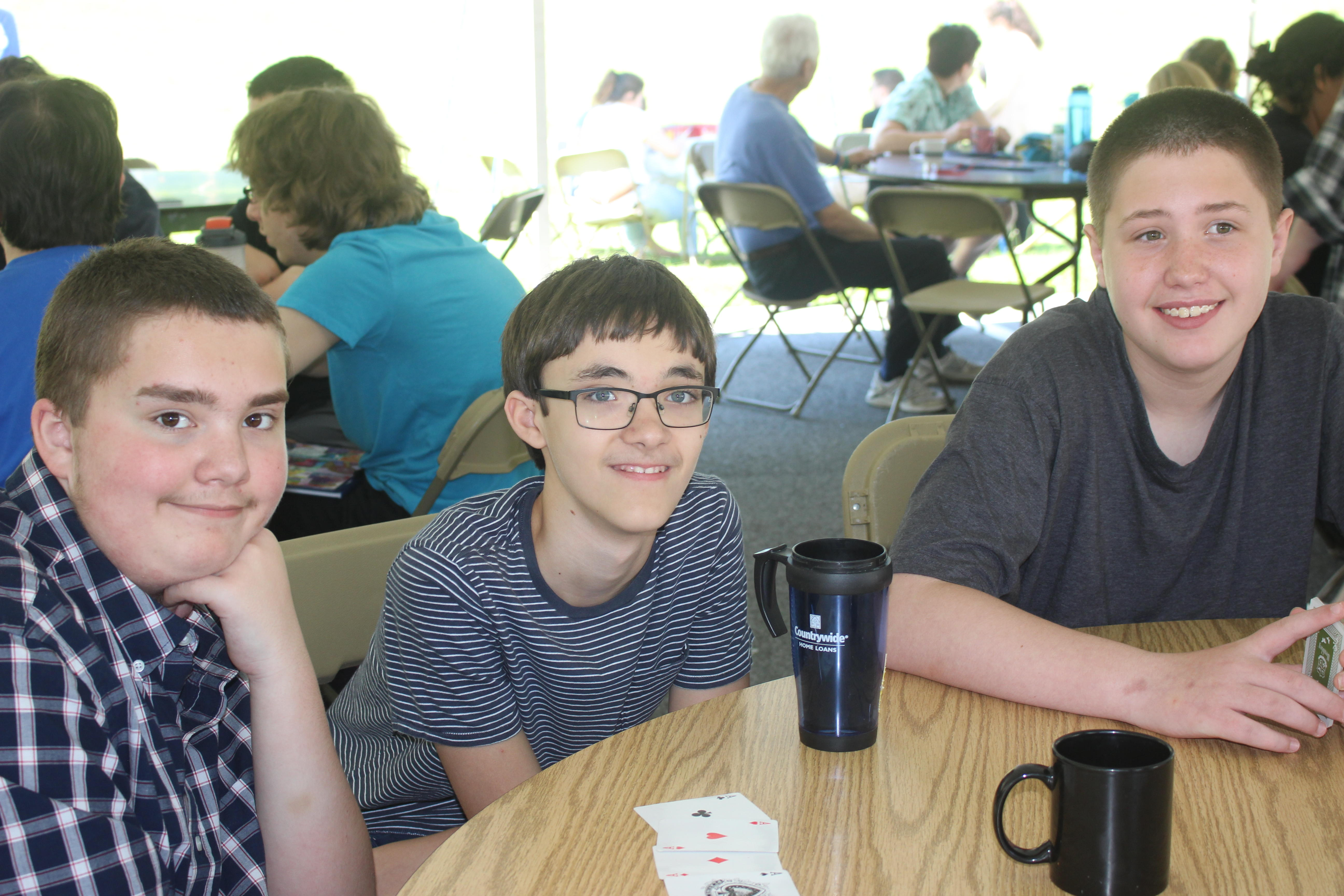 Three middle school students sitting at an outdoor table on the campus of Hunterdon Prep.