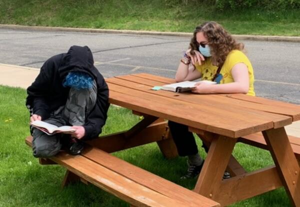 Students sitting at a picnic table reading