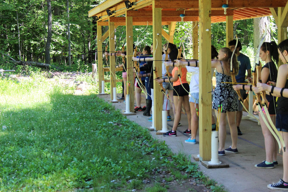 Many students participating in archery during Summer Discovery
