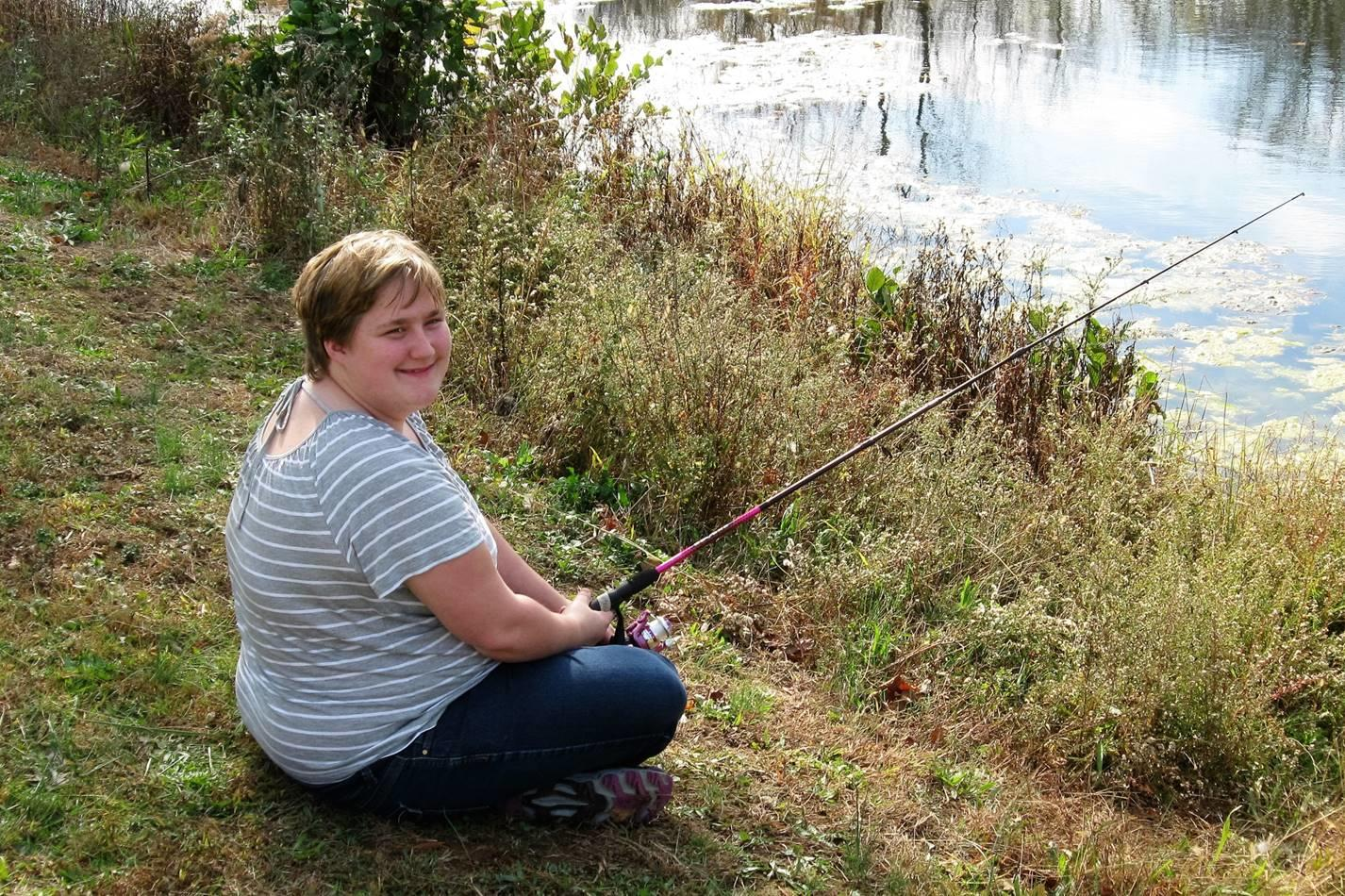 A student fishing from the bank of a pond