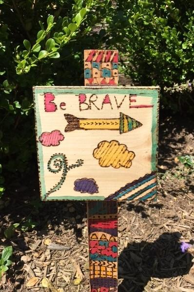"A colorful, creative wooden sign with the word ""Brave"" made by a student"