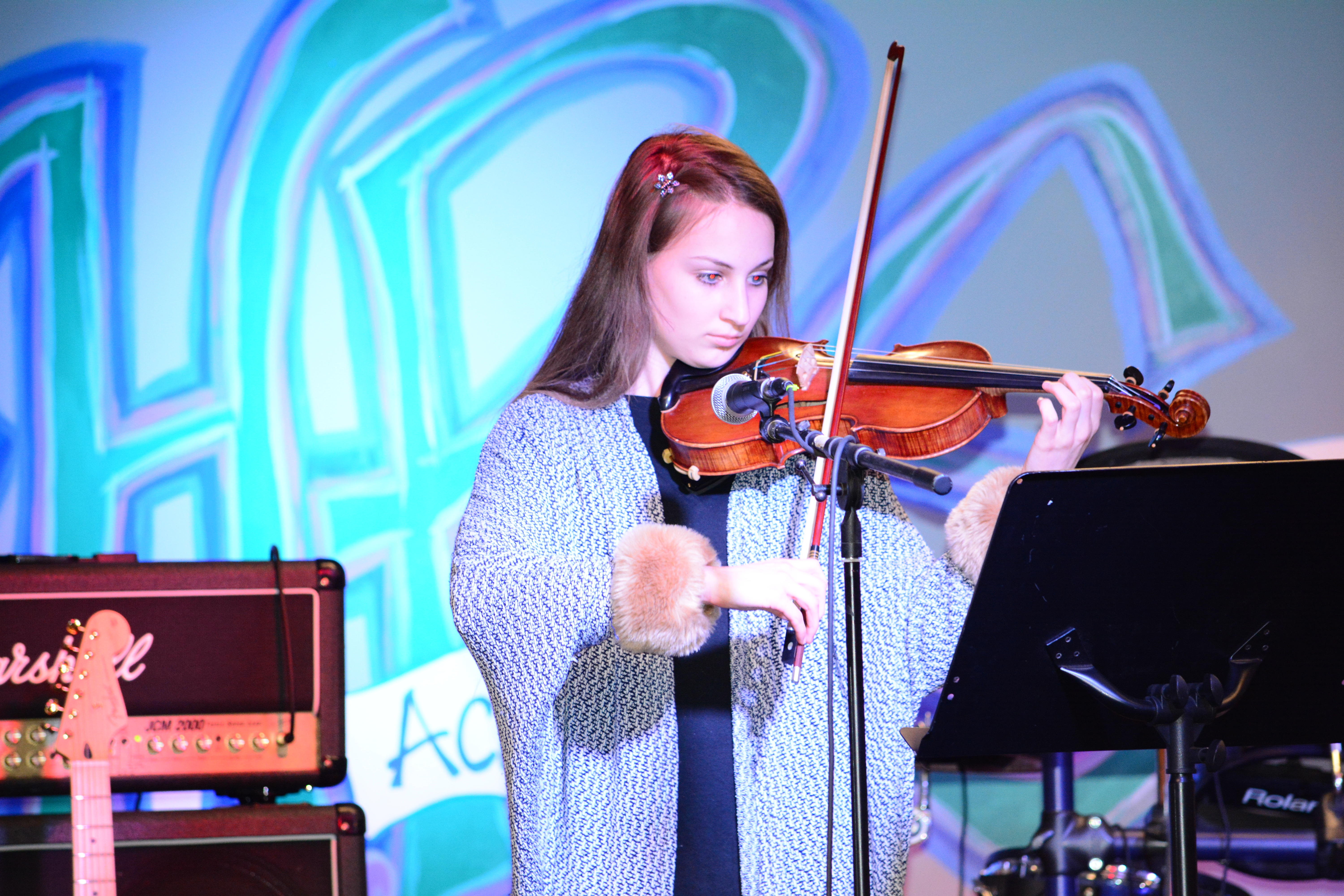 A student playing the violin at an HPS music concert