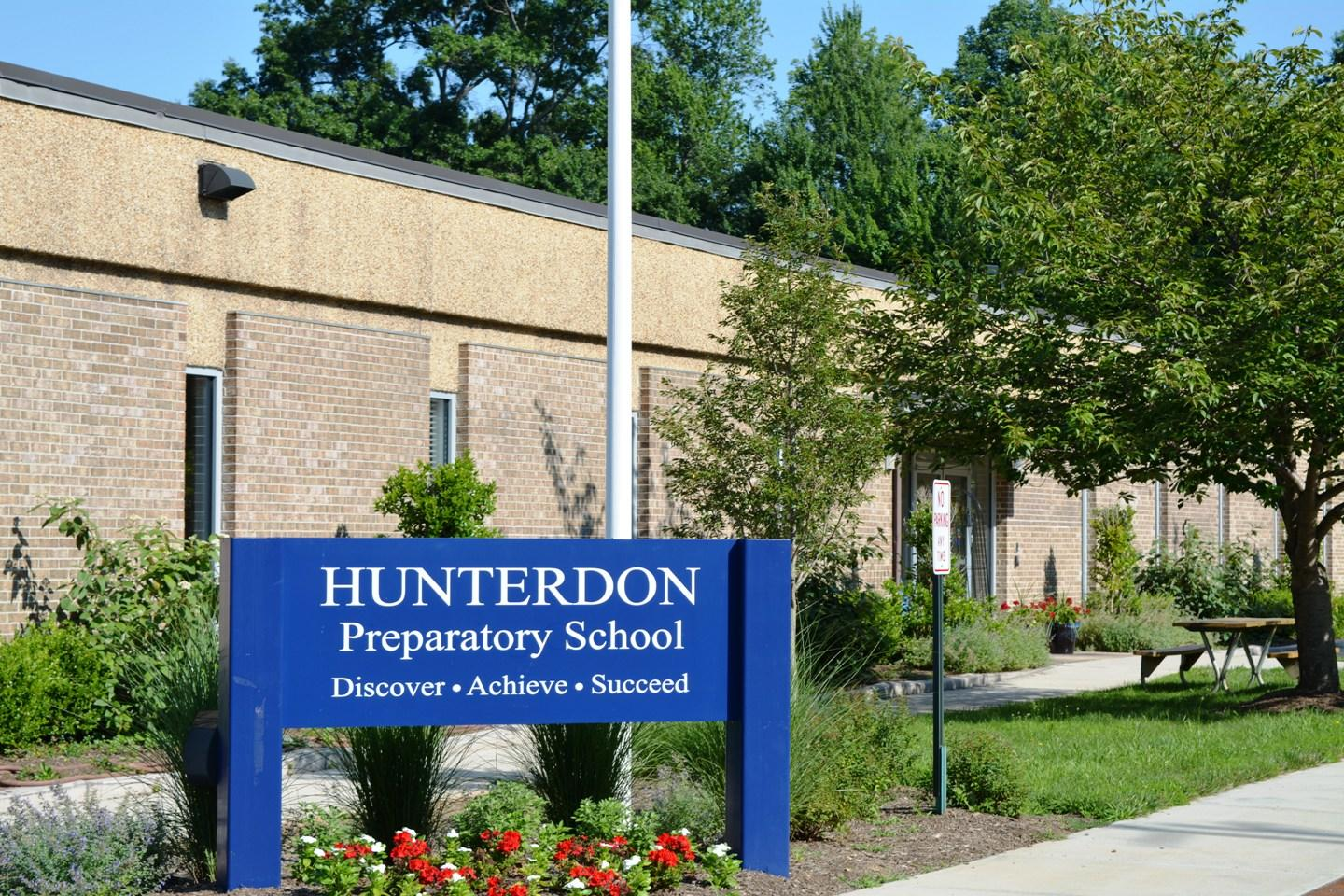 A photograph of the front of Hunterdon Preparatory School including the School Sign and motto: Hunterdon Preparatory School. Discover, Achieve, Succeed