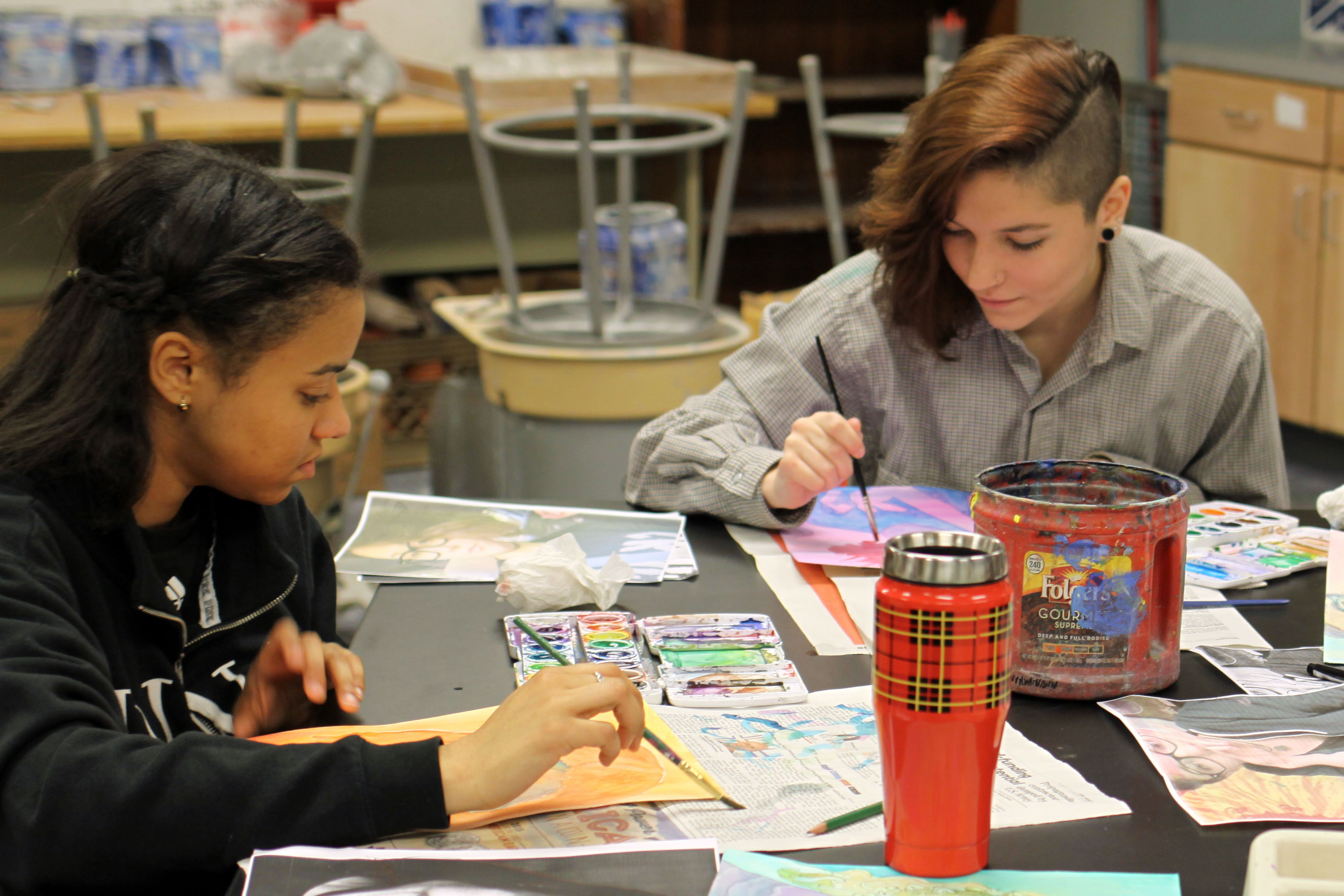 Two students working on a paint project in the Art Studio