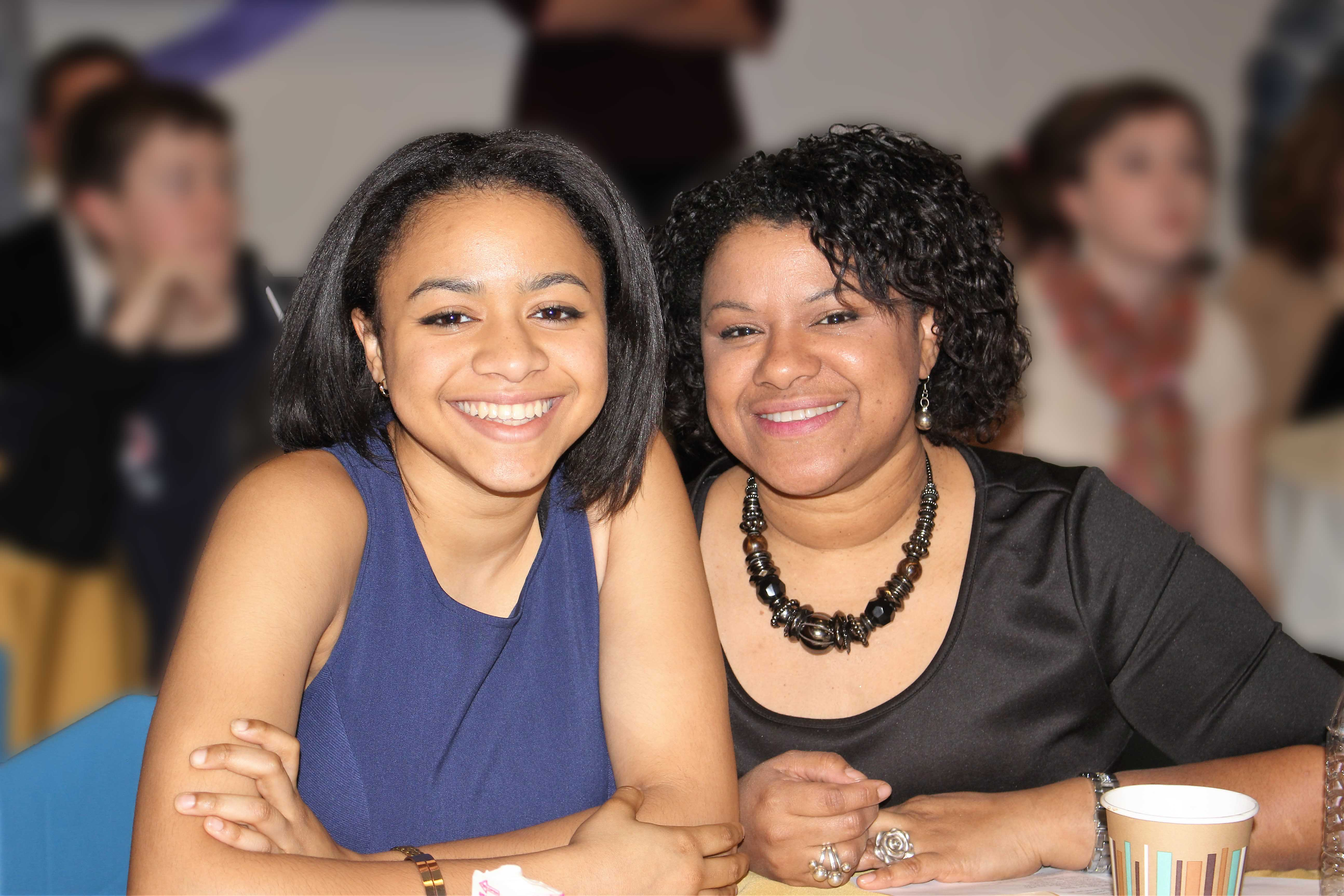 An HPS student and her mother, both smiling, at a school event.