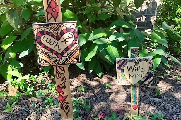 "1.	Student made signs created with wood burning techniques displayed outside the school. These say, ""with you"", and ""with me."""