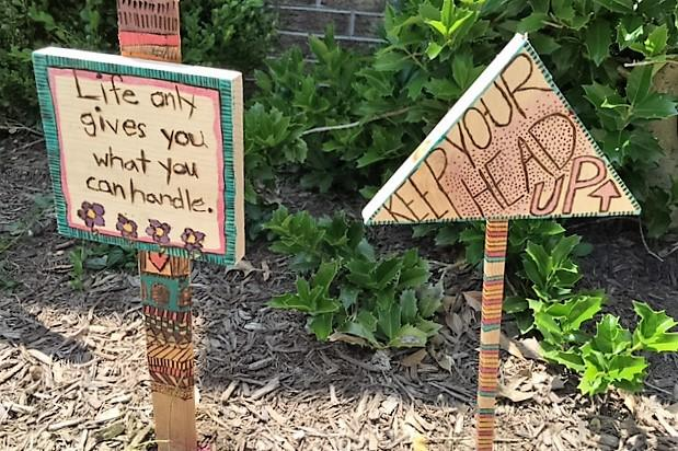 "2.	Student made signs created with wood burning techniques displayed outside the school. These say, ""life gives you what you can handle"", and ""keep your head up."""
