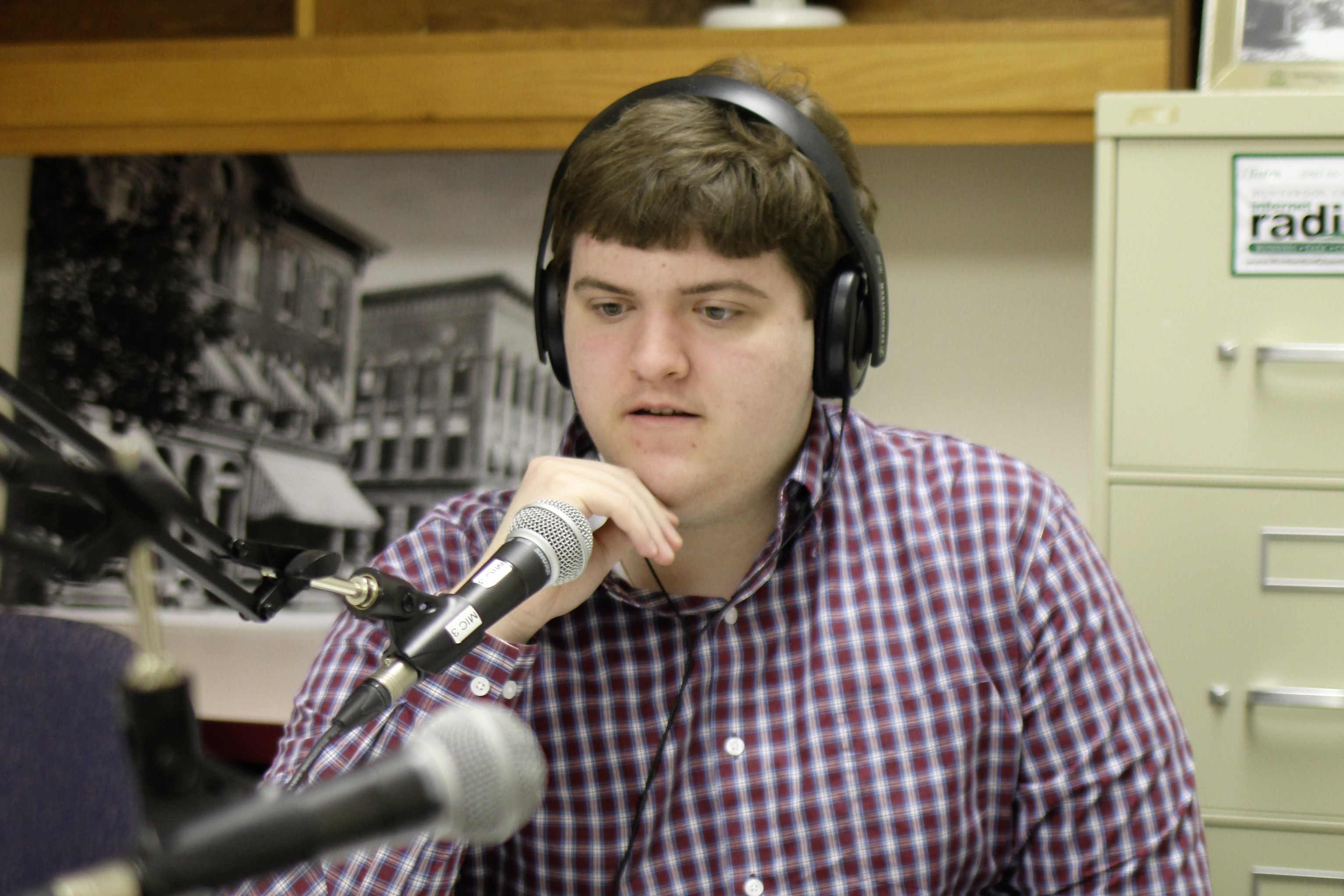 A Hunterdon Prep student wearing headphones and speaking into a microphone during a recording session at a business internship.
