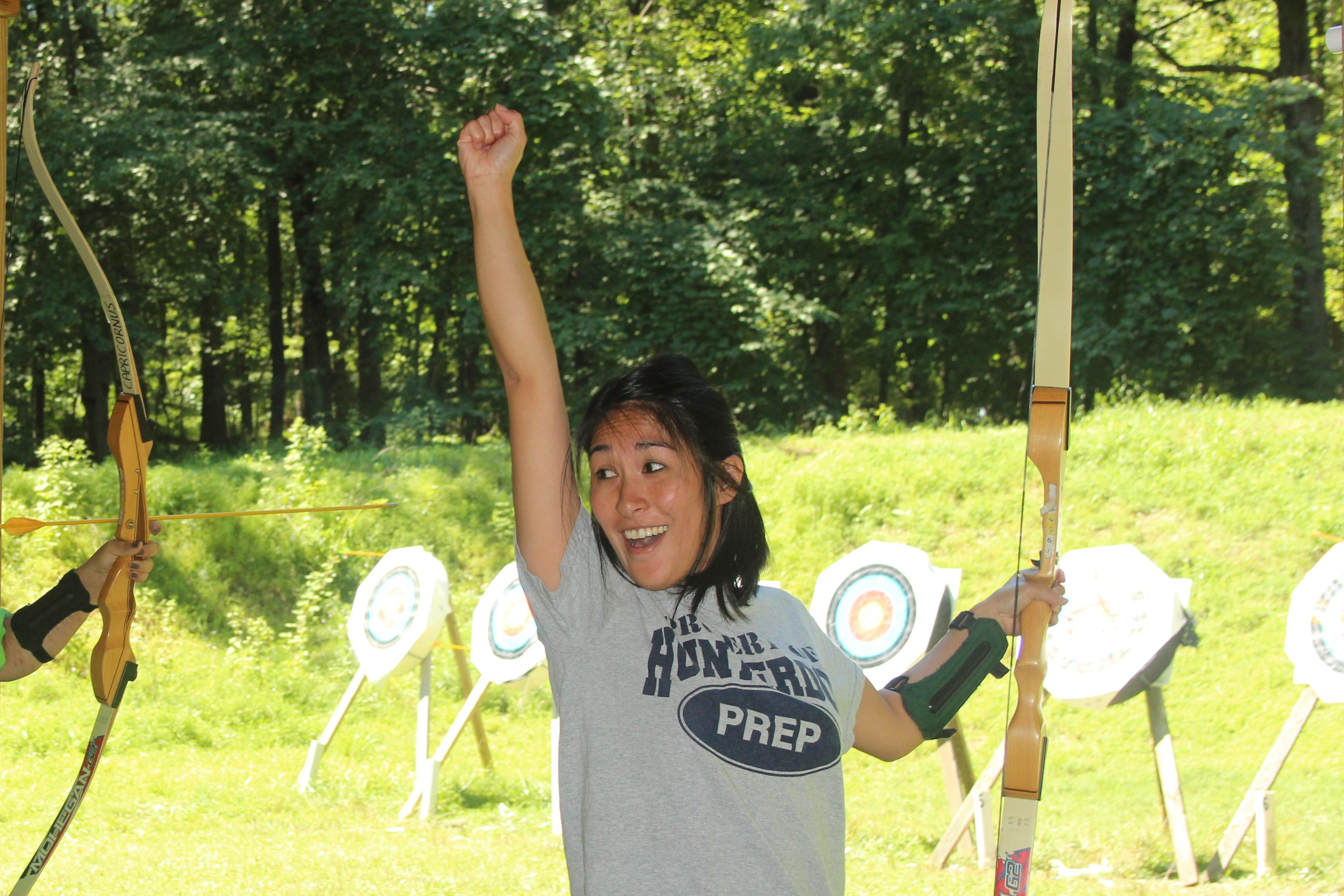 A student participating in archery, excited about her performance