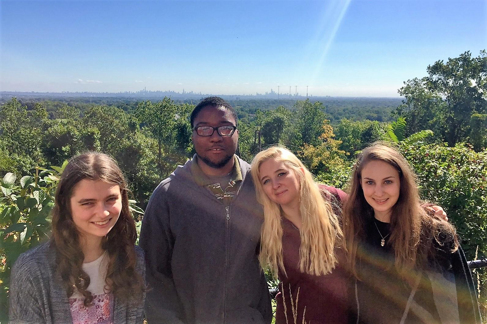 Four students on a field trip. They are on a hill with many acres of green trees behind them.
