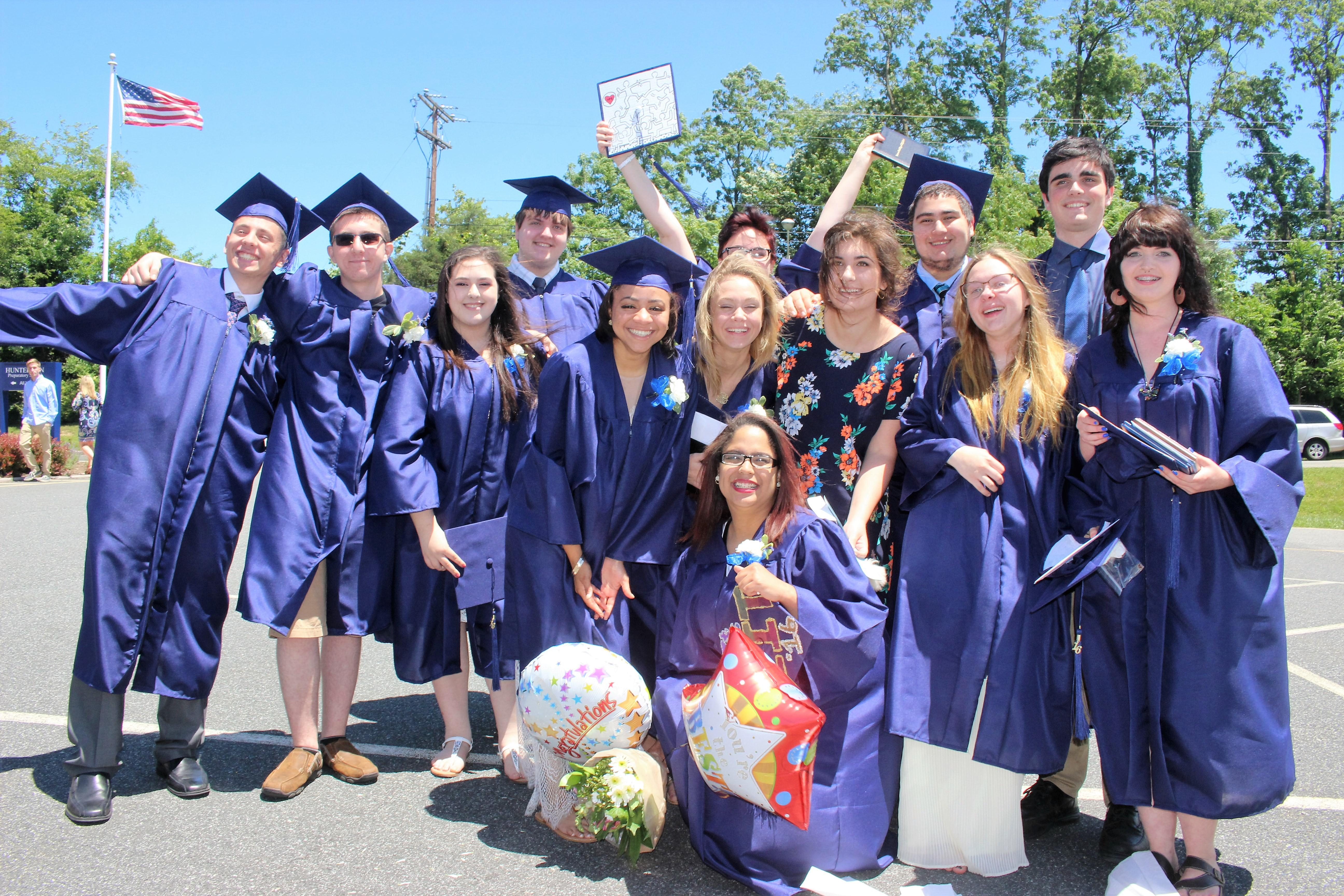 A large group of happy Hunterdon Prep students in their caps and gowns on graduation day