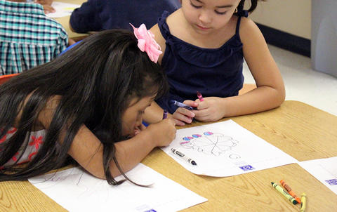 ECC female students drawing at desk, on the first day of school.