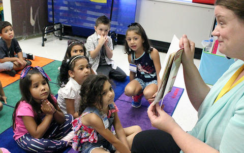 ECC teacher reading a story to her students on the first day of school.