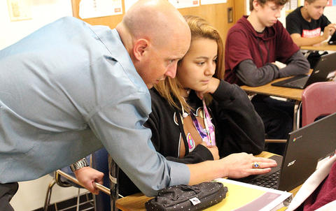 An EPHS teacher assists a student with her laptop during Google circuit training on the first day of school.