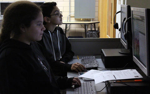 Two Elm students look at their desktop screens in darkness during Google circuit training in the computer lab.