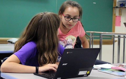 An Elm student leans over to assist her fellow student during Google circuit training.