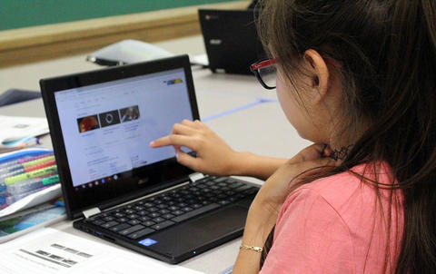 As the camera looks over her shoulder from behind, an Elm student scrolls down her laptop screen during Google circuit training.