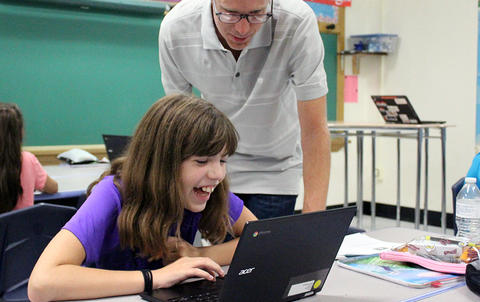An Elm student bursts out laughing while looking at her laptop screen during Google circuit training. Her teacher stands next to her, also looking at the student's screen.