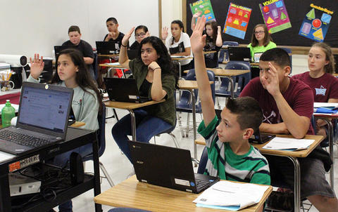 Elm students raise their hands in response to a question from their teacher during Google circuit training.