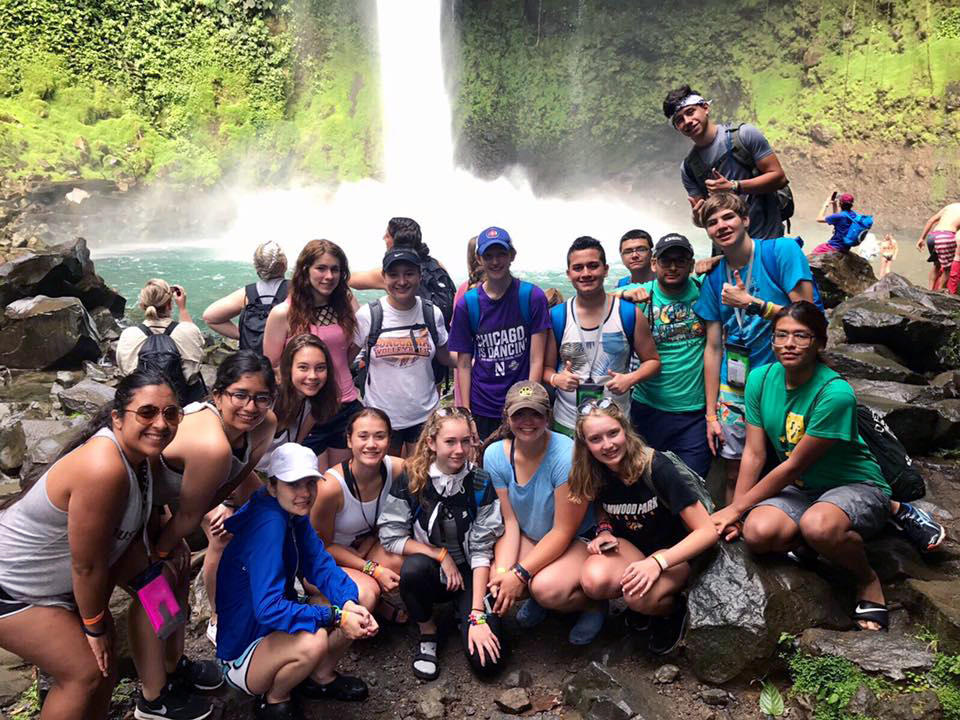 EPHS students and chaperones gather in front of a waterfall during their Costa Rica summer trip.