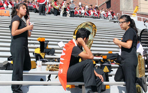 An EPHS Band member talks on her smartphone and other students converse in the stands of Memorial Stadium as they wait for the start of Illinois Band Day.