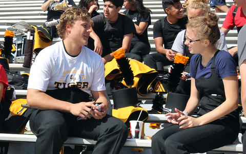 Two EPHS Band members talk while sitting in the stands at Memorial Stadium.