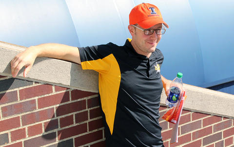 EPHS Band Director Mr. Kyle Rhoades leans against a wall at Memorial Stadium, his left hand holding a bottle of water.