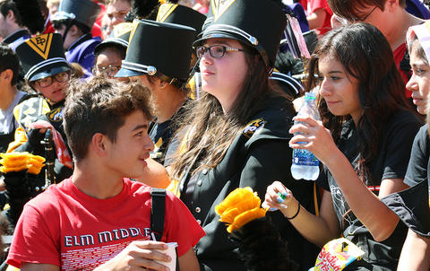 An EPHS Band member turns around in the stands at Memorial Stadium to talk to another band member as they wait for the start of Illinois Band Day.