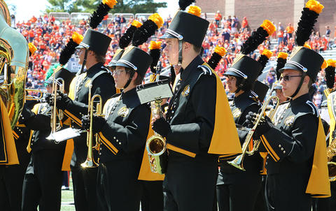 EPHS Band members stand at attention on the Memorial Stadium football field. They are facing east. The view is from their left side.