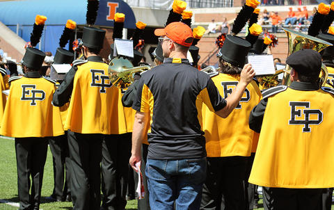 EPHS Band Director Mr. Kyle Rhoades helps a musician flip his music sheet during the halftime performance. The view is from behind as the band faces west.