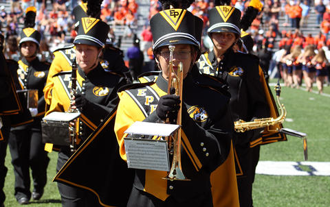 A view from the front of EPHS Band members facing east at Memorial Stadium. A trumpet player is featured. She is holding her trumpet directly in front of her as she stands at attention.