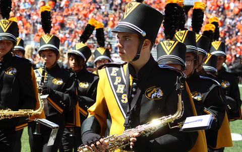 A view from the front of EPHS Band members facing east at Memorial Stadium. They have finished their halftime performance and are marching off the field. The photo focuses on a saxophone player whose head is turned south.