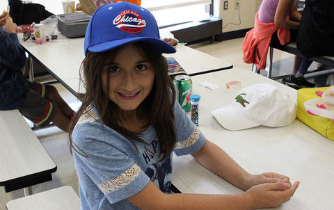 An Elmwood Elementary student seated in the school cafeteria wears a hat to support the Hats for Houston fundraiser.