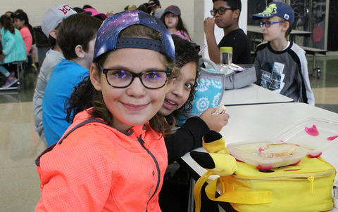 Elmwood Elementary students seated in the school cafeteria wear hats to support the Hats for Houston fundraiser.