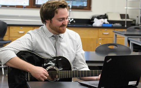 Science teacher Mr. Christian Rosenzweig, a musician on the side, plays his guitar while waiting for visitors to his classroom during EPHS Open House 2017.