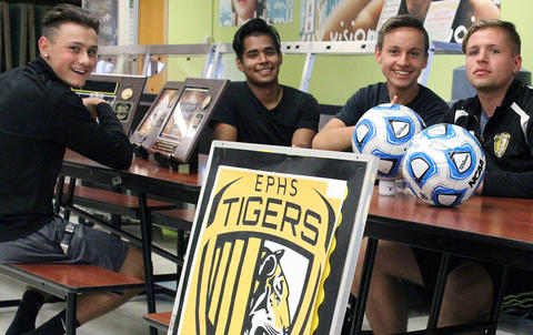 Four male soccer players sit at a display table in the cafeteria ready to answer questions during EPHS Open House 2017.