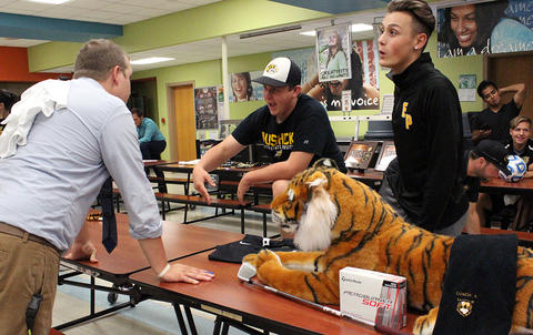 Two male athletes speak with a teacher in the cafeteria during EPHS Open House 2017.