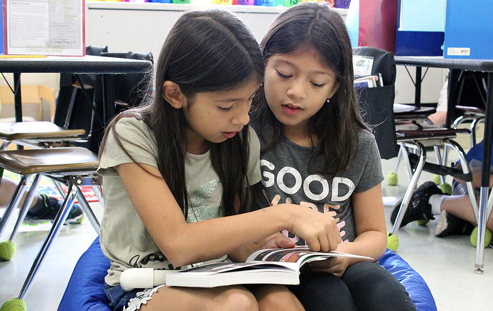 Two female students read out loud from the same book in Ms.Traci Dean's 3rd-grade class.