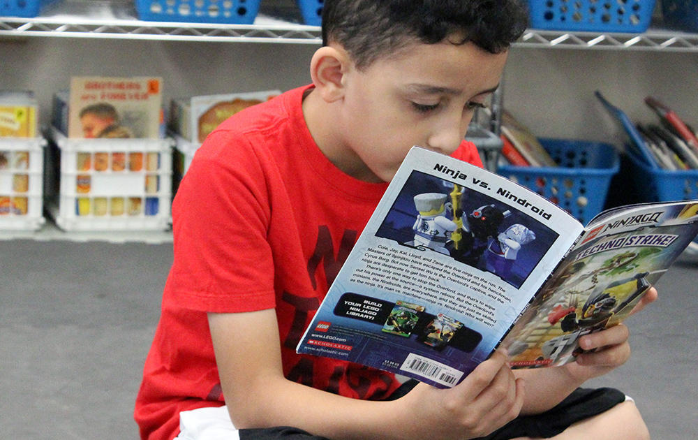 A male student sits on the floor reading a book in Ms. Traci Dean's 3rd-grade classroom.