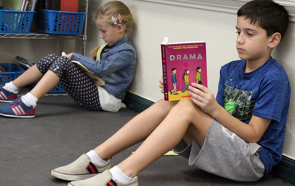 A male student in the right foreground and a female student in the left background sit on the floor reading books in Ms. Traci Dean's 3rd-grade classroom.