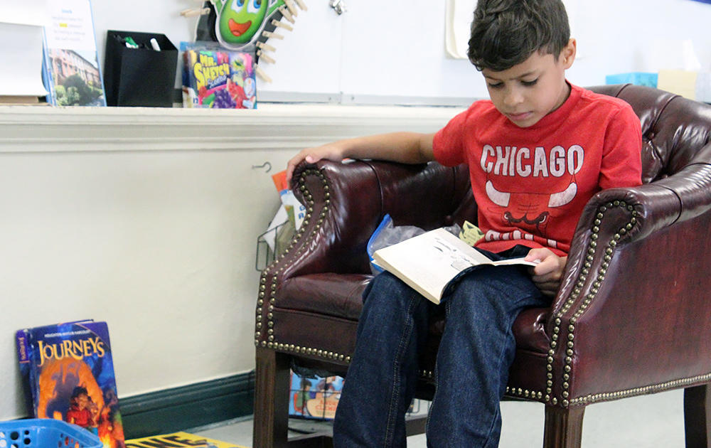 A male student sits in a comfy chair reading a book in Ms. Traci Dean's 3rd-grade classroom.