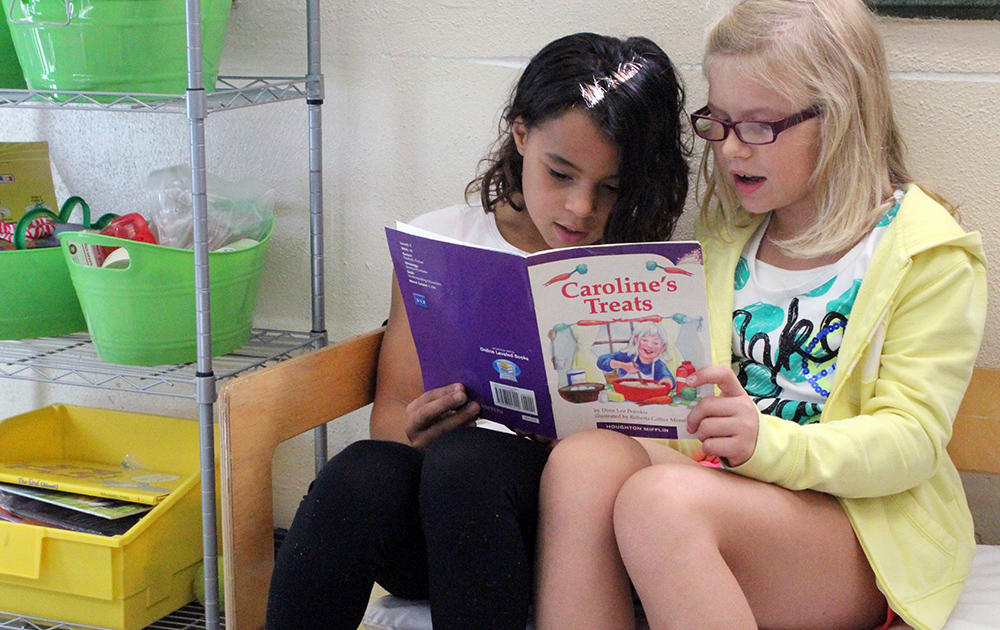 Two female students sit on a bench while sharing a book in Ms. Traci Dean's 3rd-grade classroom.