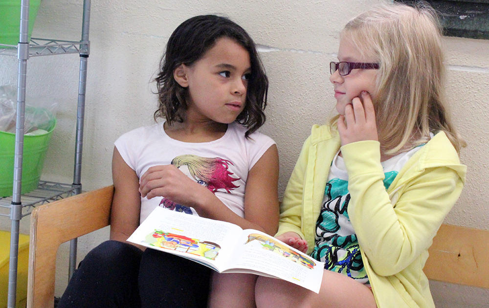 Two female student sit on a bench and puzzle out an unfamiliar word while sharing a book in Ms. Traci Dean's 3rd-grade classroom.