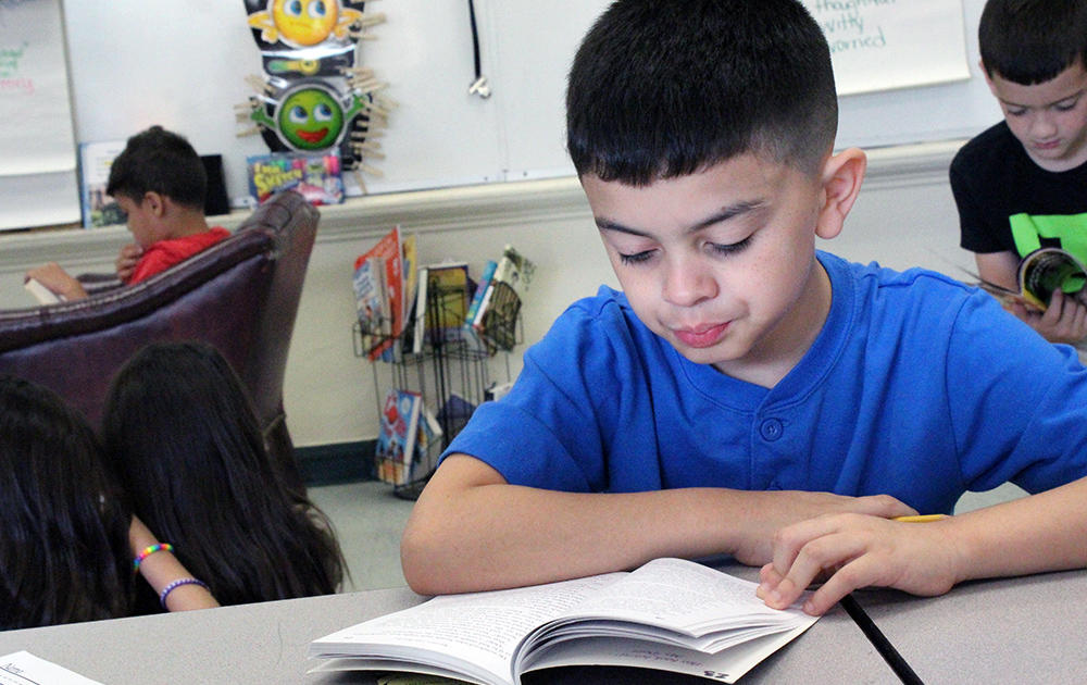A male student sits at a work table reading a book in Ms. Traci Dean's 3rd-grade classroom.